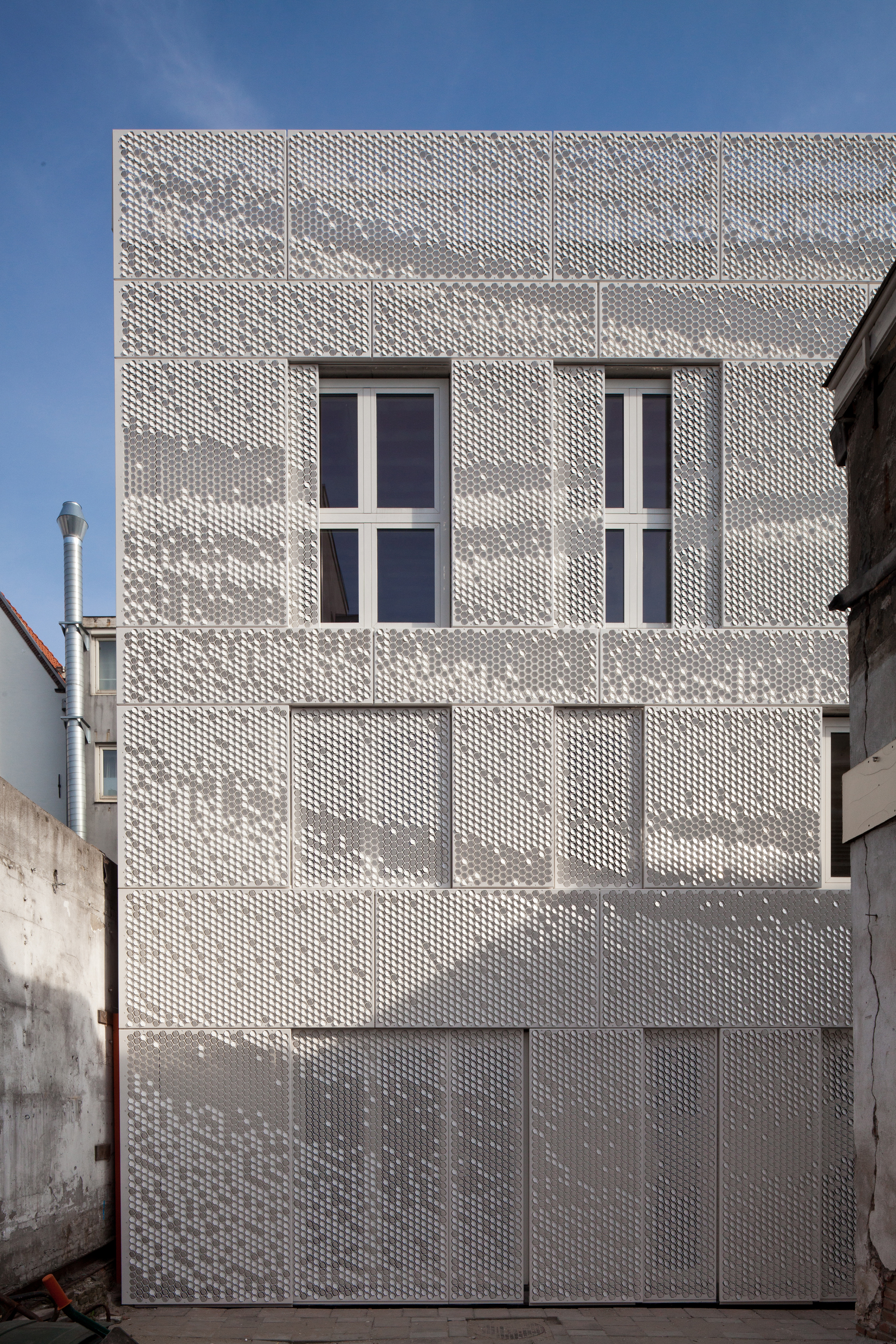 White perforated metal panels with a graphic pattern cover the faade and also double