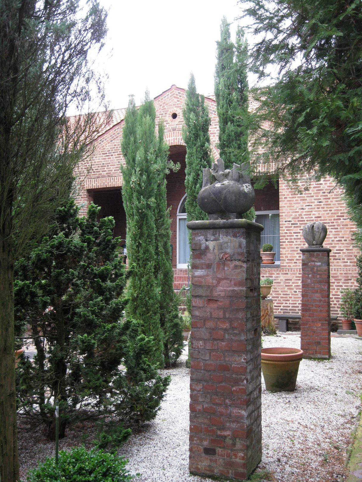 ... Brick Columns Are Topped With Concrete Vegetable Sculptures (fennel,  Eggplant And Capsicum) By