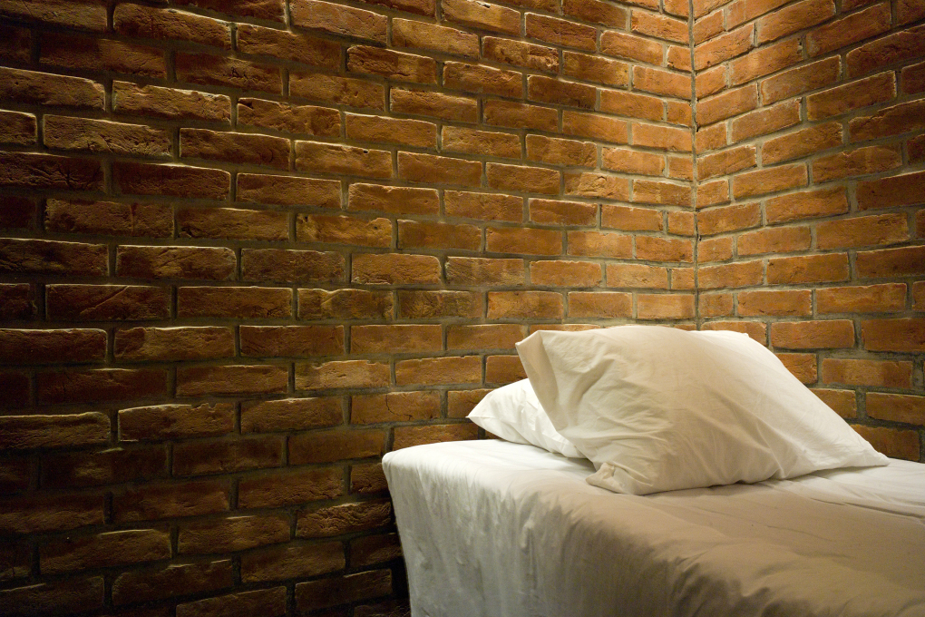 The spare simple interior of a dormitory with exposed brick. (Photo: Eric Chenal)