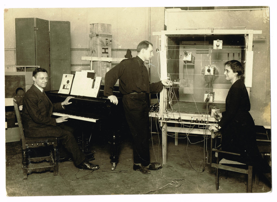 "Ludwig Hirschfeld-Mack at the piano for the staging of his ""colour, light, games"" performance, with centre F.W. Bogler, right Marli Heimann, 1924. (Photo: A. & E. Frankl, 1960 print, Ima Bauhaus-Archiv Berlin © Kaj Delugan)&am"