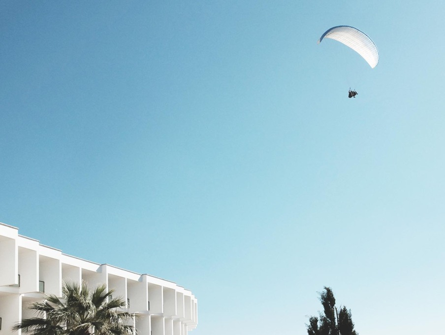 Suspended in surreality, a parachutist hovers above the curved white cellular hotel structure. (Photo: Gili Merin)