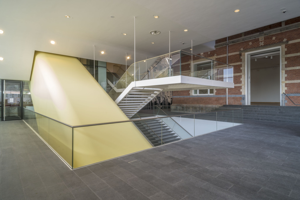 From ground level, a broad staircase leads visitors either up or down, to the two museum halls in the new part of the museum. The yellow tube contains the escalator. Photo: John Lewis Marshall