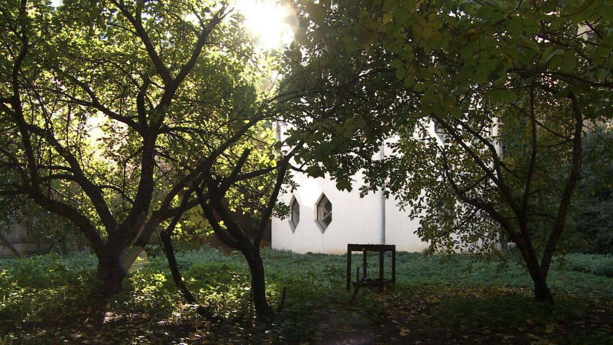 The Melnikov House glimpsed through its garden. Film still.