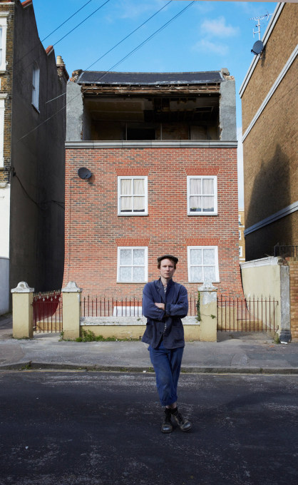 "Alex Chinneck in front of his UK installation, ""From the Knees of My Nose to the Belly of My Toes""."