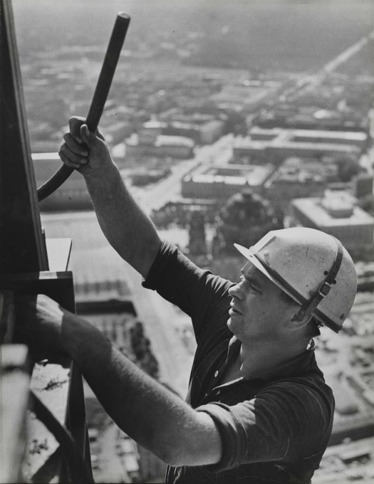 Construction work at a great height, with the city cathedral and Unter den Linden visible in the background. (Photo: Karl-Heinz Kraemer © Archive Berlinische Galerie)