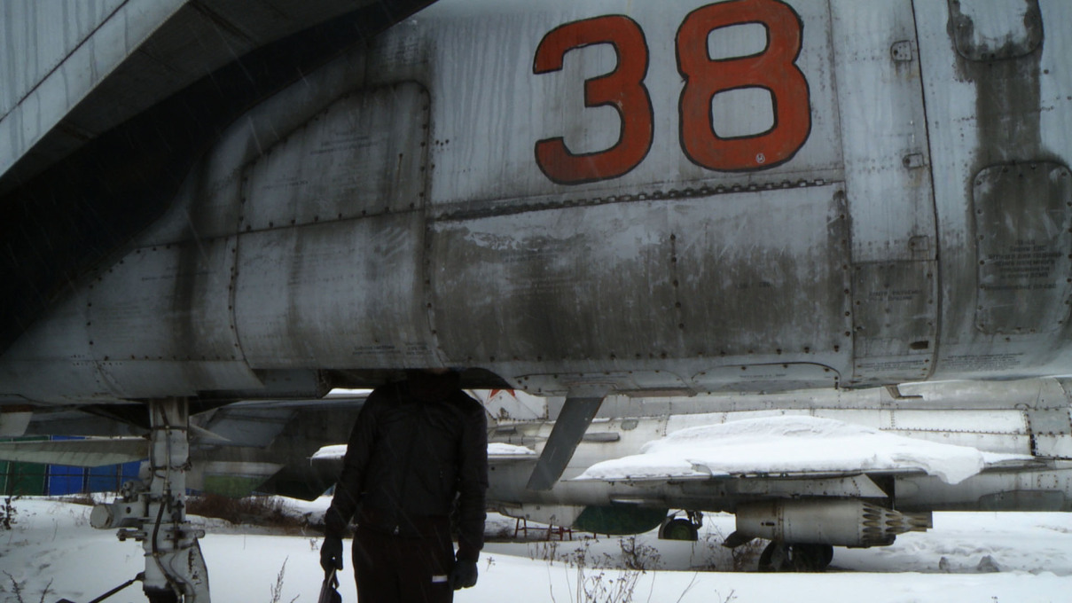 Inspecting the decaying remains of a fleet of Soviet jets. Film still.