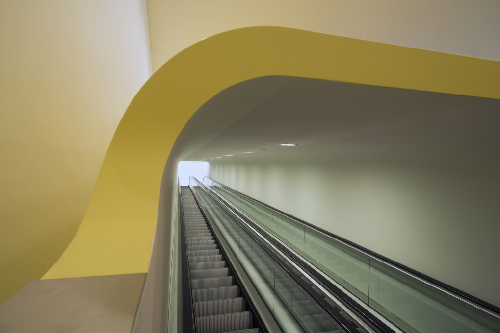 Thanks to the opaque skin of the escalator tube, visitors don't notice that they're crossing the busy entrance area when moving up or down from one hall to the next. According to the architects, this creates a continuous museum experience. Photo: John&