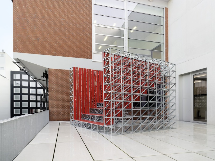 "Outside, Studio Tom Emerson, ""Fun Palace""(2014), a raked tribune made from a modular metal frame and red wooden slats, sits on the Löwenbräuareal building's upper terrace."