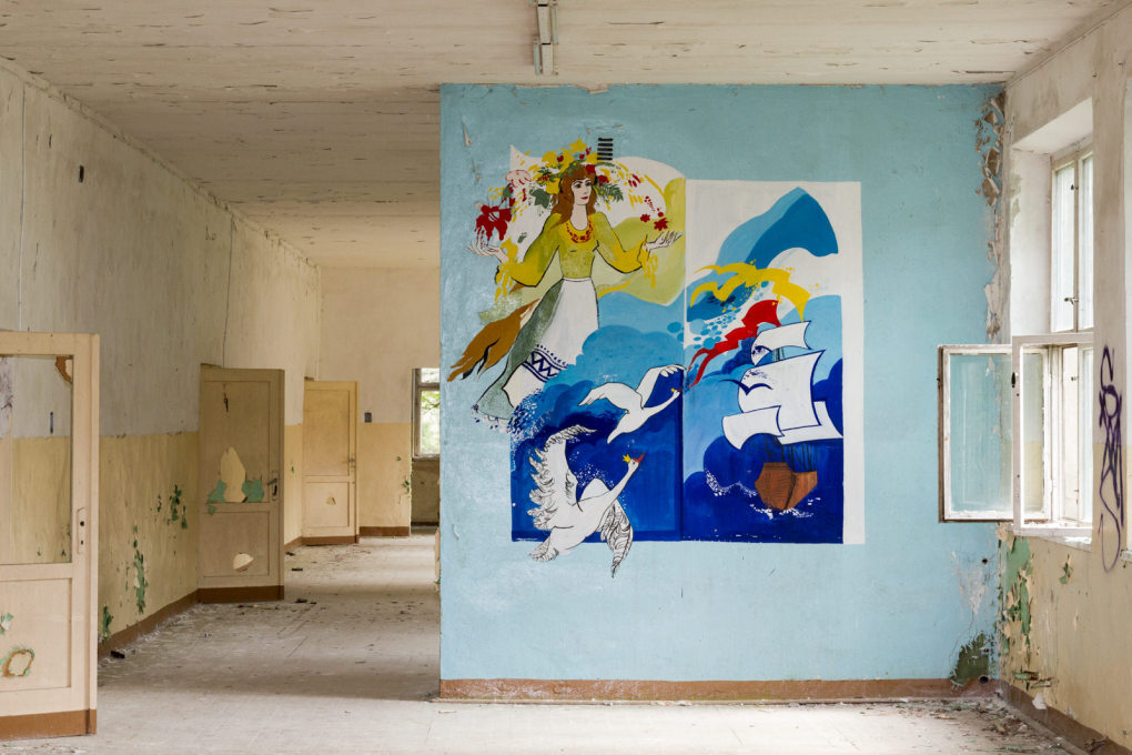 A school mural depicts a sailboat, its bright colours oddly out of place with the rather forlorn architecture.