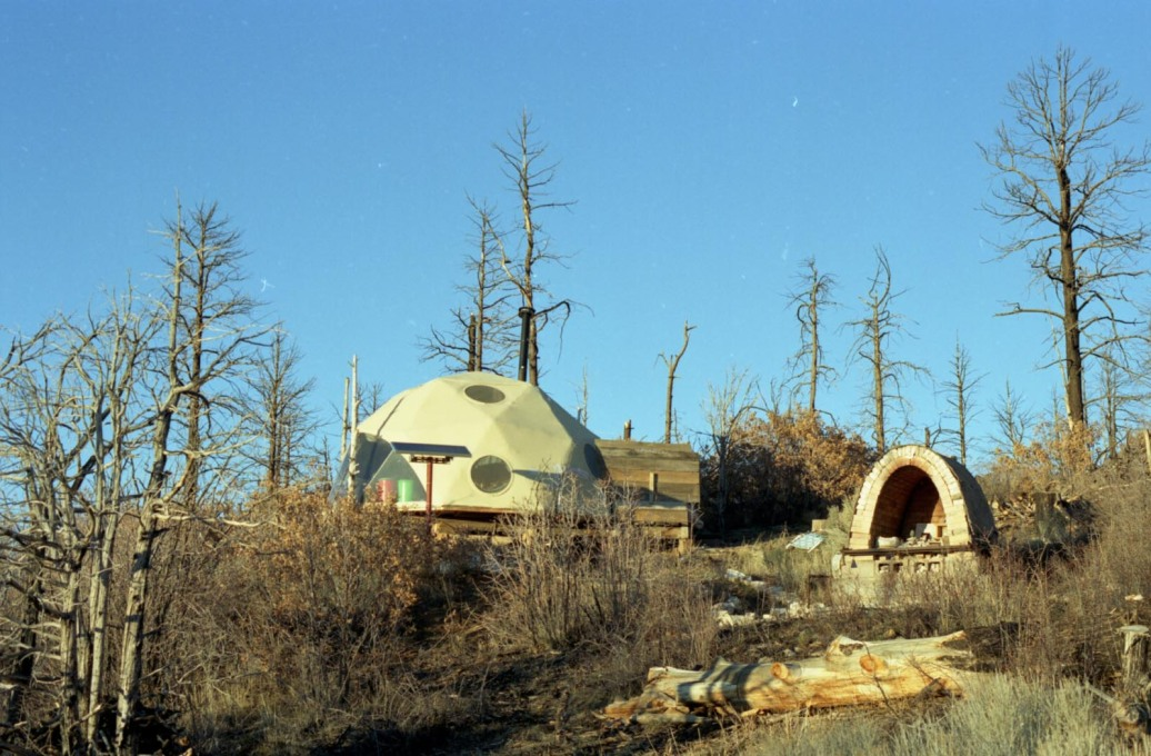 Lama Foundation: charred trees standing around provisional domes donated to residents after the devastating fire. (Photo: Oliver Croy)