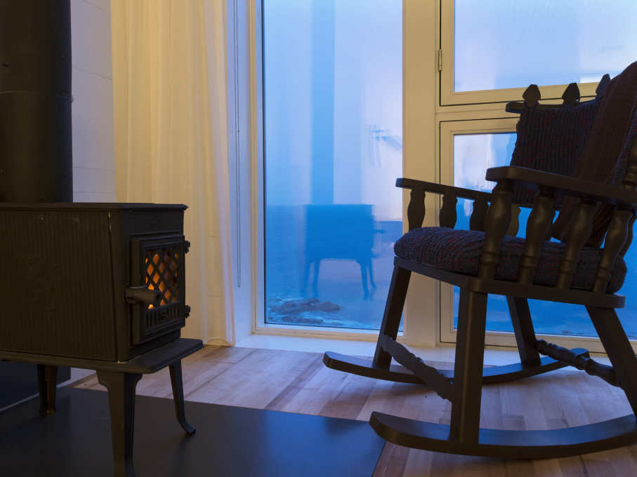 Chair, stove and well-glazed window at dusk. (Photo: Alex Fradkin)