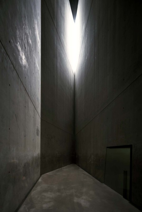 A view inside the Holocaust Tower, an unheated, empty concrete void which reaches a height of 24 metres and which is lit by a single slit at the top of the structure. (Photo © BitterBredt Photography)