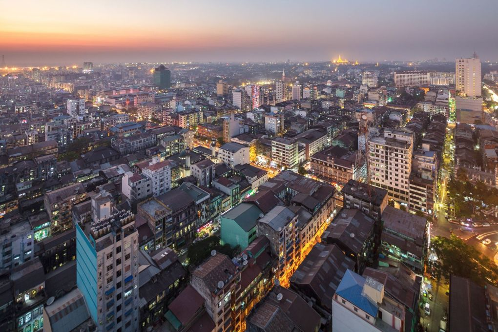 The context today. Yangon at dusk from the top of Centrepoint Towers. Downtown, the tight street grid dates from colonial days of the mid-19th century. On the horizon, glowing golden, is the Shwedagon Pagoda, Yangon's most famous landmark.