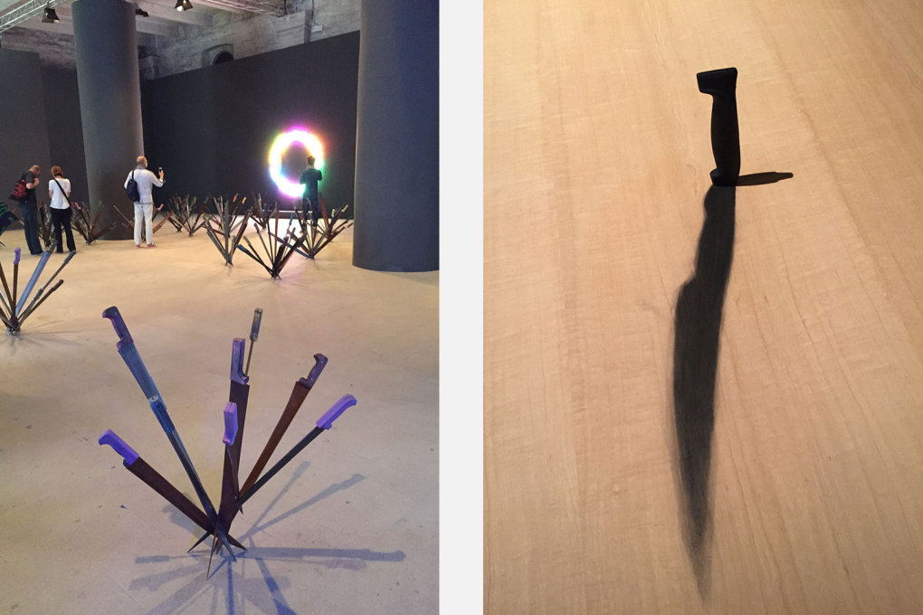 "There are a lot of weapons and knives in the Arsenale: left, Adel Abdessemed sculptures ""Nymphéas"", with Bruce Nauman neons behind, and right, a knife implanted with a painted shadow in a desk. Right: Eduardo Basualdo: ""Amenaza"
