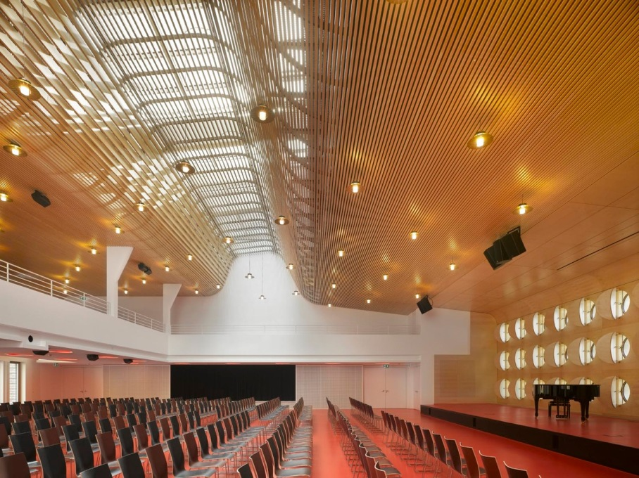 The climax of the design is the main lecture hall, lit by a skylight with a series of curved wooden baffles below gently diffusing the light. Even in this roof detailing, you find a cheerful, open feel to the architecture.