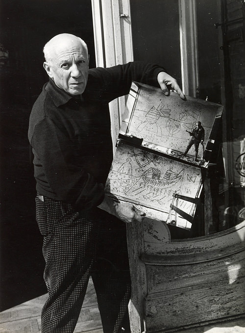 Pablo Picasso at his studio, with photographs of the work in progress on the murals (Photo: C. Nesjar, ca. 1959)