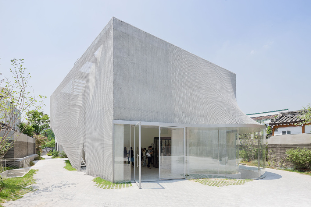 The glass facade breaks the concrete and mesh form, and allows views into the building from the rear. (Photo: Iwan Baan)