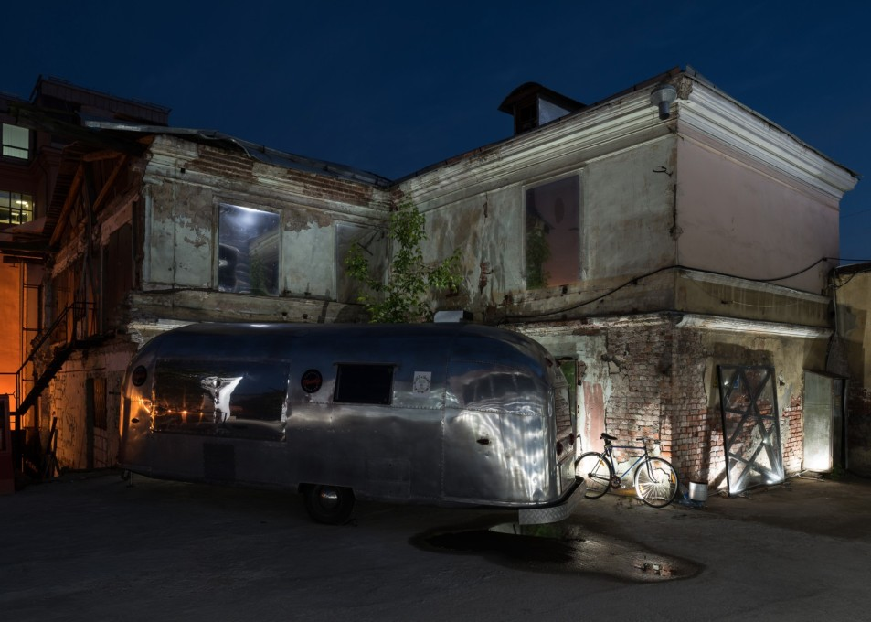 Contrasting textures of old building fabric, shiny pipe-insulation foil cladding and silver airstream caravan.