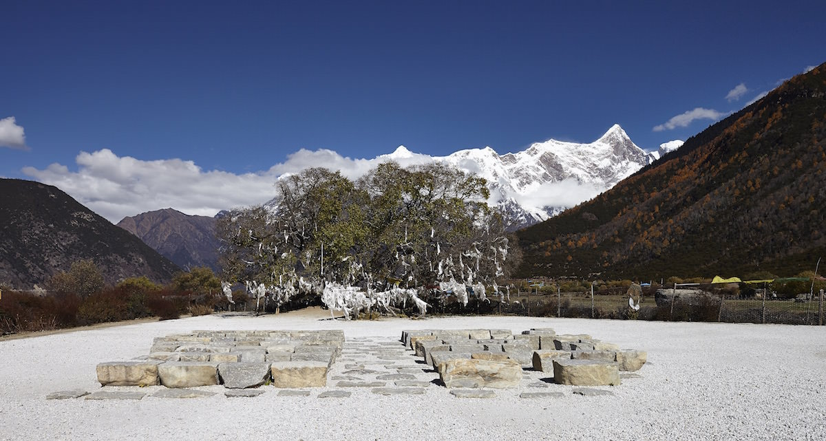 The place of contemplation in Tibet that standardarchitecture created by disposing roughly hewn boulders of local stone as seating in front of a panorama of a 1,300 year old mulberry tree backed by the 7,782 peak of the Namcha Barwa mountain.
