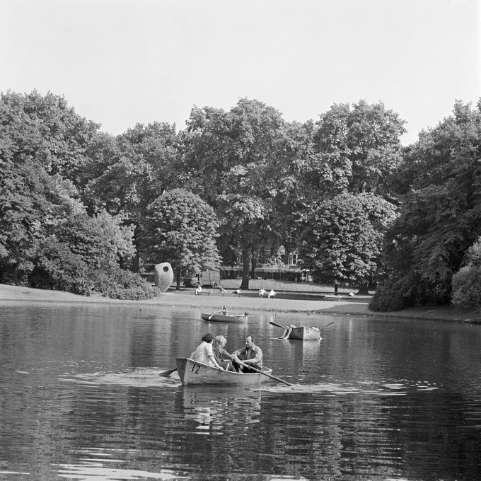 """Single Form"" by Barbara Hepworth forms a backdrop for rowing on the boating lake at Battersea Park, London, 1962 - 1964. (© Historic England)"
