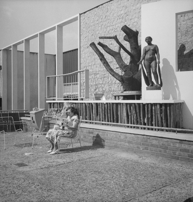 A visitor relaxes in front of the Homes and Gardens pavilion at the South Bank Exhibition during the Festival of Britain, 1951. (© Historic England)