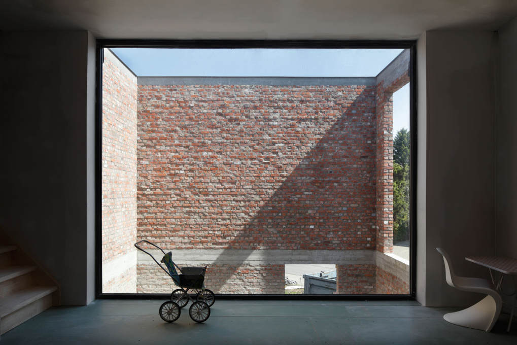 On completion, the two-storey high patio brings daylight into the heart of the house, visually making the raw brick walls a integral background element in the interior.