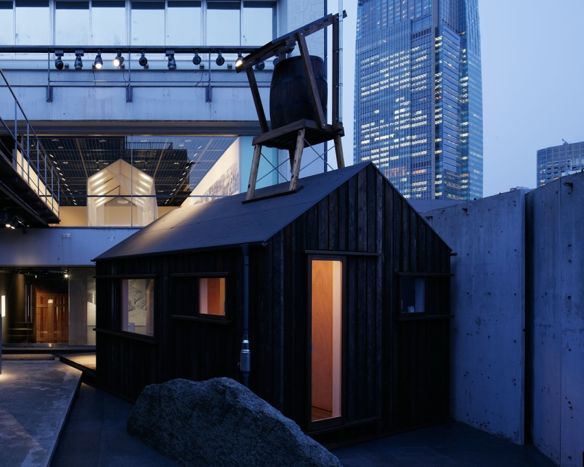 Yoshifumi Nakamura's Hanem Hut at dusk, its door ajar, its simple form and the glow from inside, an invitation to dwell, underlying the poetic and pragmatic spirit that infuses the whole exhibition. (Photo: Nacása & Partners Inc.)&