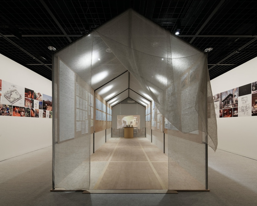 In the upstairs gallery, a structure sheathed in mosquito netting displays the design and construction drawings of Yoshifumi Nakamura's Hanem Hut, the one full-sized example in the exhibition. (Photo: Nacása & Partners Inc.)&a