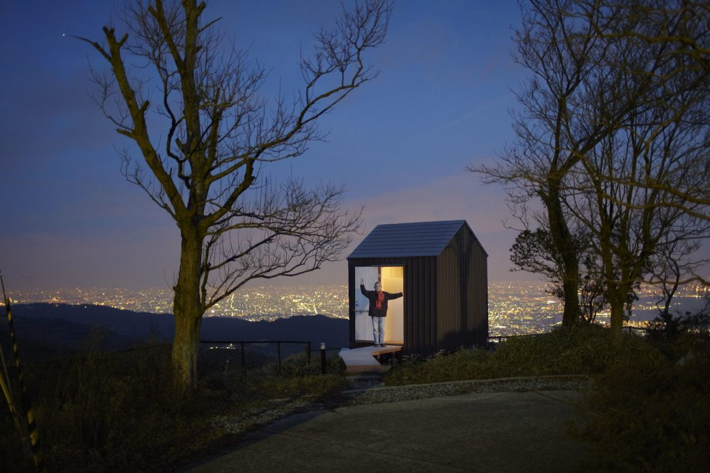 "The curator of the exhibition ""Come on-a My Hut!"", architect Yoshifumi Nakamura, standing at dusk in the doorway of one of his projects, Luna Hut in Hyogo, built in 2012. (Photo: Hideya Amemiya)"