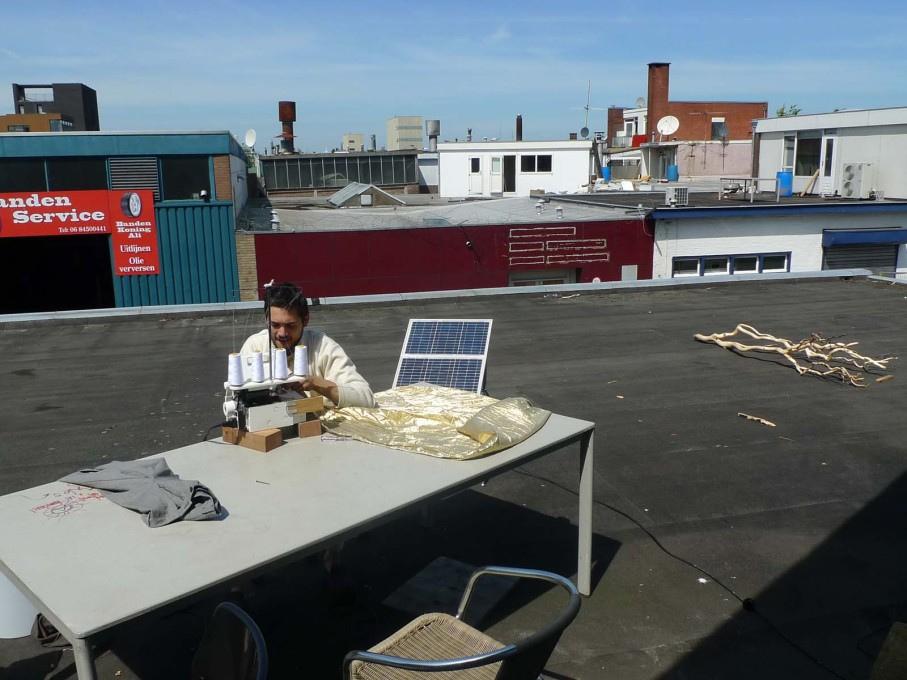 Sewing on solar power and car batteries with a view across the rooftops from the roof terrace.