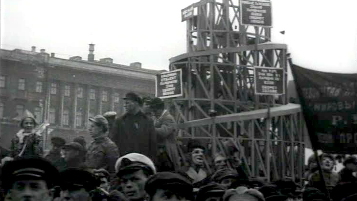 Archival newsreel footage of a Soviet parade, with a wooden model of Vladimir Tatlin's Monument to the Third International (1919-20) carried through the streets. Film still.