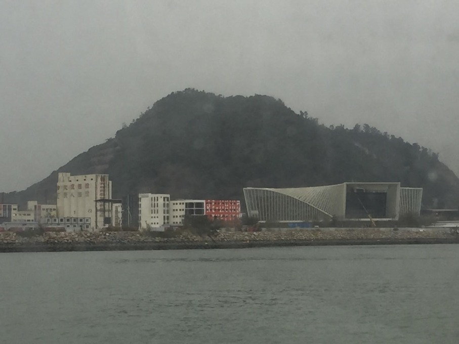 The Dacheng Flour Factory site of the Biennale, as seen from the ferry from Hong Kong, dwarfed by the China Merchants' marketing pavilion to the right. (Photo: Rob Wilson)